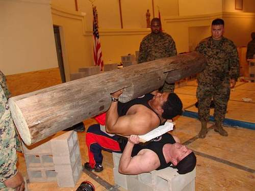 Brett keller with a bed of nails and tim spigner bench pressing a log while laying